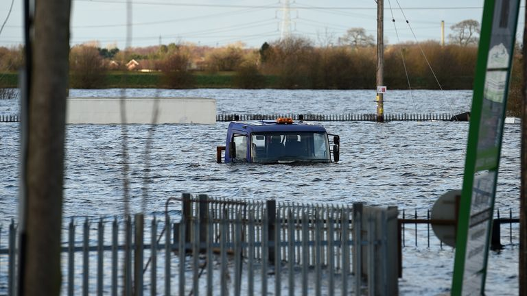 Flood water surrounds a lorry, stuck on a flooded road in Snaith, northern England