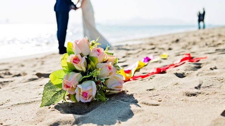 Wedding couple with bouquet on beach.
