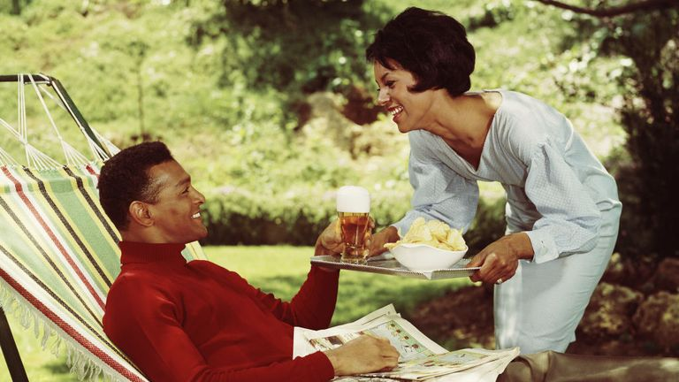 A wife bringing her husband beer and potato chips while he relaxes in a hammock in the garden, circa 1965. (Photo by L. Willinger/FPG/Getty Images)