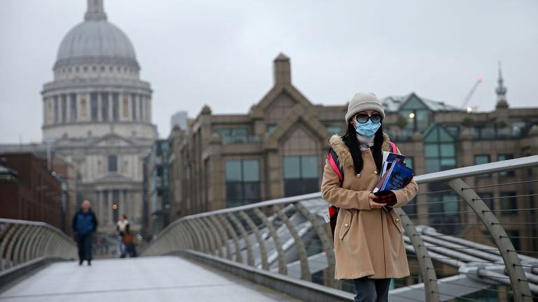Woman wears surgical mask in central London