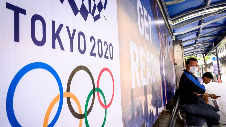 A man wearing a face mask sits next to an advert for the Tokyo 2020 Olympics at a bus stop in Bangkok