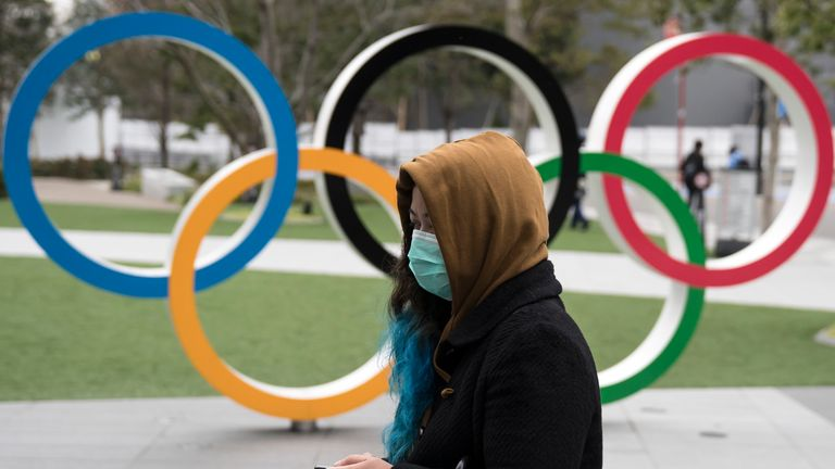 TOKYO, JAPAN - FEBRUARY 26: A woman wearing a face mask walks past the Olympic rings in front of the new National Stadium, the main stadium for the upcoming Tokyo 2020 Olympic and Paralympic Games, on February 26, 2020 in Tokyo, Japan. Concerns that the Tokyo Olympics may be postponed or cancelled are increasing as Japan confirms 862 cases of Coronavirus (COVID-19) and as some professional sporting contests are being called off or rescheduled and some major Japanese corporations ask for people t