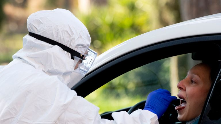 A woman at the wheel of her car undergoes a drive-through swabbing test for coronavirus at the Santa Maria della Pieta' hospital in Rome on April 3, 2020 during the country's lockdown aimed at curbing the spread of the COVID-19 infection, caused by the novel coronavirus. (Photo by Tiziana FABI / AFP) (Photo by TIZIANA FABI/AFP via Getty Images)