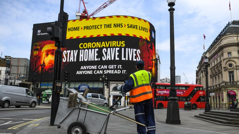 LONDON, ENGLAND - APRIL 08: A street cleaner is seen in front of Coronavirus messaging on Picadilly Circus on April 8, 2020 in London, England. Prime Minister Boris Johnson was transferred to the intensive care unit at St Thomas' Hospital after his coronavirus symptoms worsened on Monday night. (Photo by Peter Summers/Getty Images)