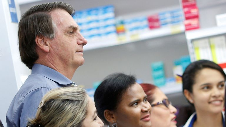 Brazil's President Jair Bolsonaro poses for pictures with employees of a drugstore, amid the coronavirus disease (COVID-19) outbreak, in Brasilia, Brazil, April 10, 2020. REUTERS/Adriano Machado