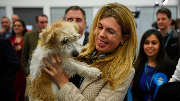TOPSHOT - Carrie Symonds, partner of Britain's Prime Minister and Conservative leader Boris Johnson, holds their dog, a Jack Russell-cross named Dilyn, as she arrives at the count centre in Uxbridge, west London, on December 13, 2019 while votes were counted as part of the UK general election. - Prime Minister Boris Johnson's ruling party appeared on course for a sweeping victory in Thursday's snap election, an exit poll showed, paving the way for Britain to leave the EU next month after years of political deadlock. (Photo by Oli SCARFF / AFP) (Photo by OLI SCARFF/AFP via Getty Images)