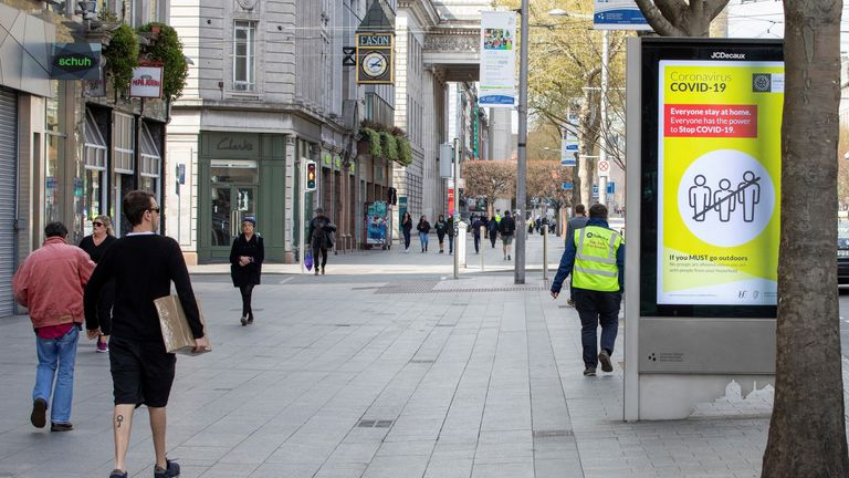 A pedestrian passes a poster alerting the public that if they must leave their home, they must stay within a two kilometre or 20 minute walking distance radius of their home, in Dublin city centre on April 8, 2020, as life in Ireland continues during the nationwide lockdown to combat the novel coronavirus pandemic. - Irish police set up nationwide traffic checkpoints on Wednesday, armed with new powers to enforce a lockdown designed to stem the spread of the coronavirus. Emergency legislation passed in the Irish parliament two weeks ago allows the government to curb non-essential travel during the crisis. People violating the ban risk a fine of up to 2,500 euros ($2,700) and/or six months in prison. The roadblocks have been put in place ahead of Easter holidays, traditionally used as an occasion for travel in Ireland. (Photo by PAUL FAITH / AFP) (Photo by PAUL FAITH/AFP via Getty Images)