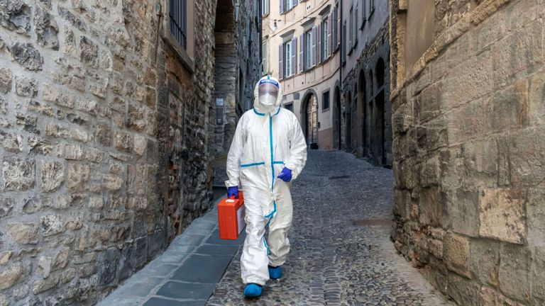 BERGAMO, ITALY - APRIL 3: (EDITORIAL USE ONLY) A member of the Italian Red Cross walks through an alley in the old town during his home visit to COVID-19 positive patients on April 3, 2020 in Bergamo, Italy. The number of new COVID-19 cases appears to be decreasing in Italy, including in the province of Bergamo, one of its hardest-hit areas. But as the infection rate slows, life is still far from normal. A local newspaper, the Eco di Bergamo, estimates that the province has lost roughly 4,800 people to coronavirus - almost twice an official tally that only counts hospital deaths - and everyone here knows someone who's fallen ill: a neighbor, a family member, a relative, a friend or an acquaintance. The Italian Red Cross, which runs an ambulance service here, continues to field constant calls for help. With only a small portion of its 600-person volunteer crew and 38 paid staff able to report for duty, those who remain work shifts of up to 20 hours long. (Photo by Marco Di Lauro/Getty Images)