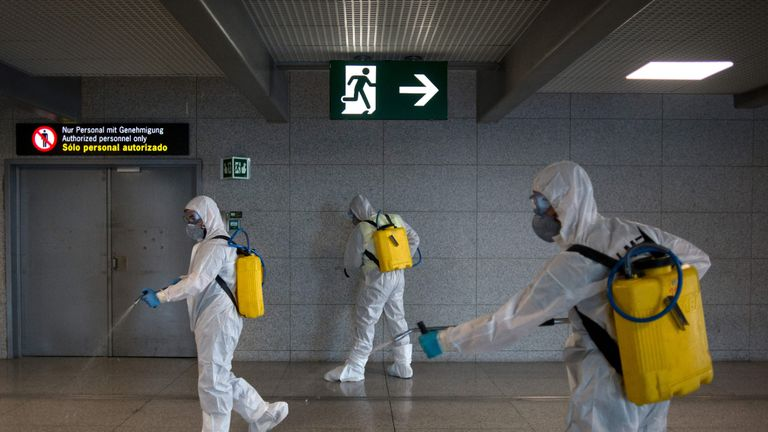 Members of the Military Emergencies Unit (UME) carry out a general disinfection at Malaga airport on March 16, 2020. - Spain has registered nearly 1,000 new COVID-19 infections over the past 24 hours, raising the total number of cases to 8,744. In order to rein in the virus, Spain has declared a state of alert, shutting all but essential services and ordering its population of 46 million people to stay at home. People are only authorised to go out to buy food or medicine, to go to work or to get medical treatment. (Photo by JORGE GUERRERO / AFP) (Photo by JORGE GUERRERO/AFP via Getty Images)