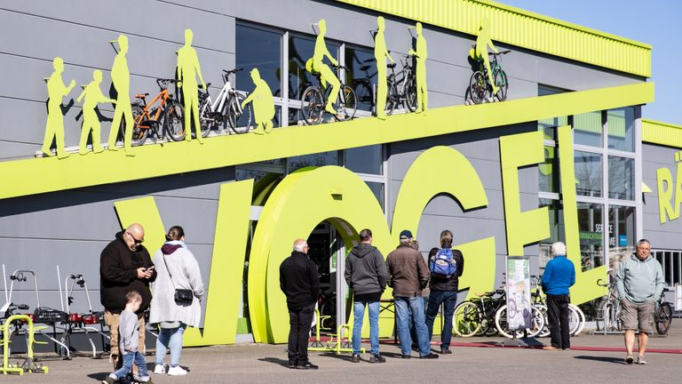 DINSLAKEN, GERMANY - APRIL 20: Costumers wait outside a bike store on the first day of the easing of some restrictions during the coronavirus crisis on April 20, 2020 in Dinslaken, Germany. Across Germany today many states, but not all, are introducing steps to lift restrictions that have had a deep economic and social impact, including the reopening of smaller-size stores, allowing high school students to take exams and restarting production lines in some factories. The number of Covid-19 infections is continuing to rise, but at a slower rate than in previous weeks, which is giving the federal and state governments hope that the time is right to begin lifting restrictions. (Photo by Lars Baron/Getty Images)