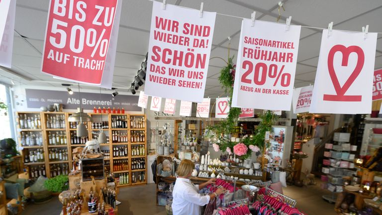 "A banner reading ""We are back! Nice to see you again"" hangs in a shop as a woman looks at clothes in Ludwigsburg on April 20, 2020. - Germany  starts easing its lockdown restrictions from April 20, 2020 and allows the re-opening of shops with a maximum sales area of up to 800 square meters. (Photo by THOMAS KIENZLE / AFP) (Photo by THOMAS KIENZLE/AFP via Getty Images)"