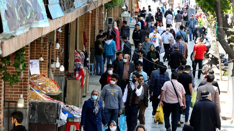 Iranians, some wearing protective gear amid the COVID-19 pandemic, shop on a street by the Grand Bazaar market in the capital Tehran, on April 18, 2020. - Iran allowed some shuttered Tehran businesses to reopen on April 18, despite the Middle East's deadliest coronavirus outbreak, as many faced a bitter choice between risking infection and economic ruin. (Photo by ATTA KENARE / AFP) (Photo by ATTA KENARE/AFP via Getty Images)