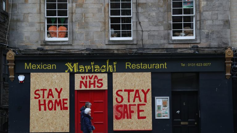 People pass a boarded up restaurant in Edinburgh which has been painted with an NHS supporting message as the UK continues in lockdown to help curb the spread of the coronavirus.