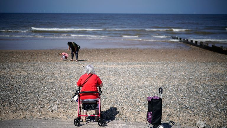 RHYL, WALES - APRIL 22: People take an exercise break on the beach during the pandemic lockdown on April 22, 2020 in Rhyl, Wales. The British government has extended the lockdown restrictions first introduced on March 23 that are meant to slow the spread of COVID-19. (Photo by Christopher Furlong/Getty Images)