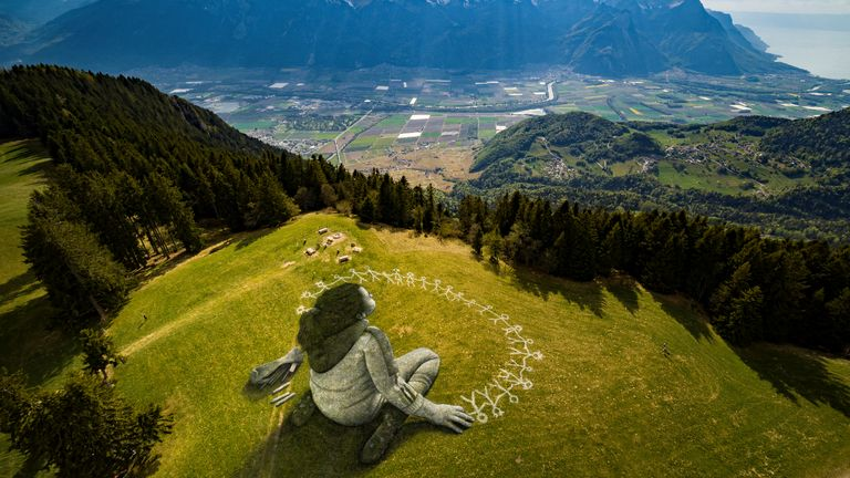 "An artwork called ""Beyond Crisis"" by French artist Guillaume Legros aka Saype and created with an eco paint made out of chalk and coal over a 3000 sqm field is pictured during the coronavirus disease (COVID-19) outbreak in Leysin, Switzerland, April 24, 2020 in this picture obtained by Reuters April 26, 2020.  Valentin Flauraud/SAYPE/Handout via REUTERS THIS IMAGE HAS BEEN SUPPLIED BY A THIRD PARTY. NO RESALES. NO ARCHIVES     TPX IMAGES OF THE DAY"