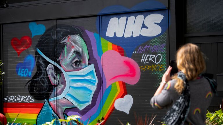 A woman takes a photograph of graffiti in support of the NHS in southeast London as the UK continues in lockdown to help curb the spread of the coronavirus.