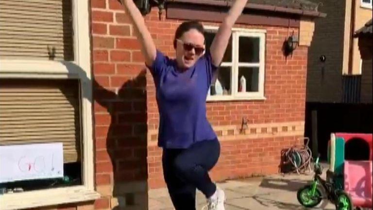 Emma Edgoose celebrates finishing her 2.6 challenge run around her garden