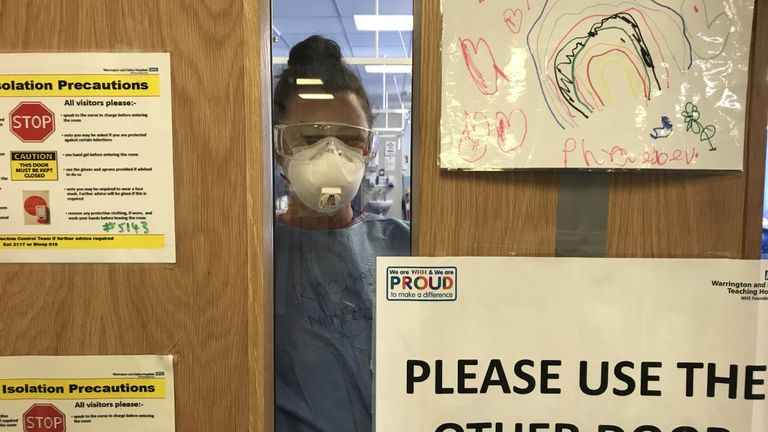 "A hospital worker looks through the door from the coronavirus ""hot site"" in A&E"