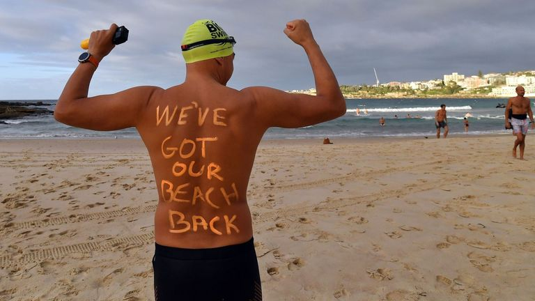 A man gets ready to enjoy his first swim in five weeks at Bondi Beach in Sydney after it reopens following closure over the coronavirus outbreak