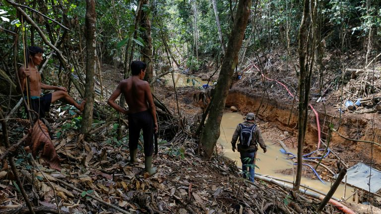 Yanomami indians follow agents of Brazil's environmental agency in a gold mine during an operation against illegal gold mining on indigenous land, in the heart of the Amazon rainforest, in Roraima state, Brazil April 17, 2016
