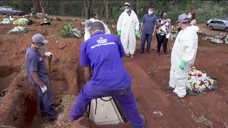 Workers dig graves for what the Brazilian president calls a 'light flu'