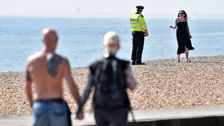 A police officer talks to a woman on the beach in Brighton, as the sunny bank holiday weather tests resolve