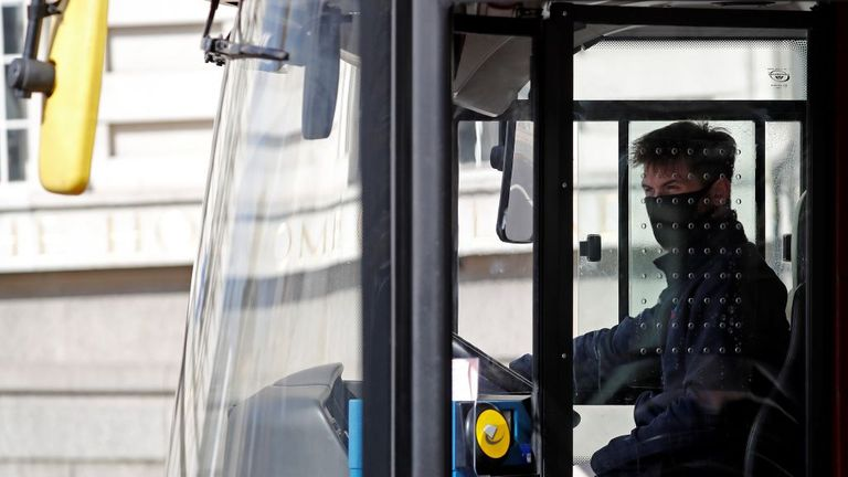 A bus driver wears a face mask while working in London