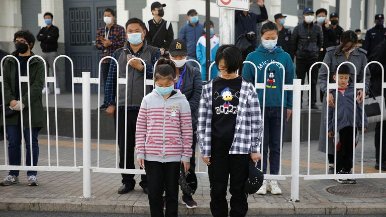 People wearing face masks stand on the street to pay tribute as China holds national mourning for those who died of the coronavirus disease (COVID-19)