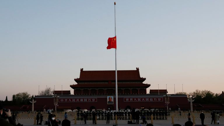 The Chinese national flag flies at half-mast during sunrise at Tiananmen Square in Beijing, as China holds a national mourning for those who died of the coronavirus disease