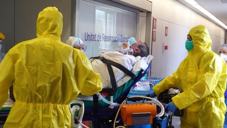 A patient is moved by doctors in full protective gear at the hospital in Barcelona