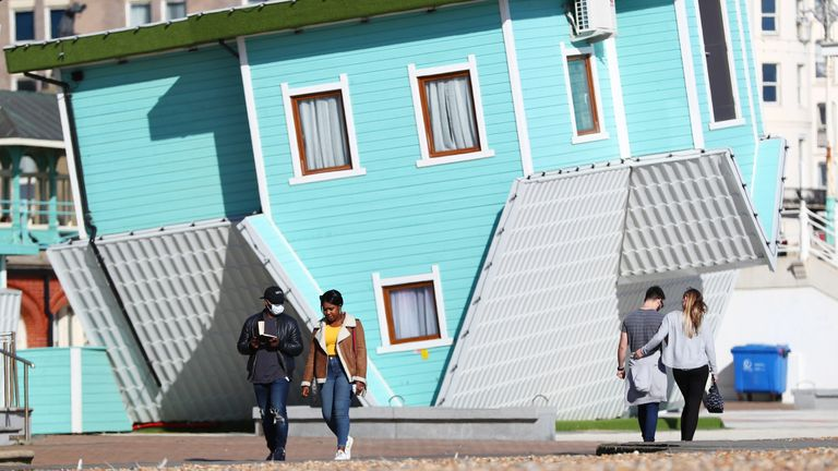 Members of the public walk past the Upside Down House next to Brighton beach