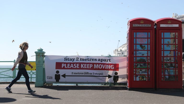 A person makes their way past a sign asking people to stay 2 metres apart on Brighton sea front