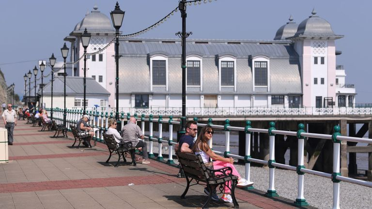 PENARTH, WALES - APRIL 25: People enjoy the spring sunshine whilst social distancing on Penarth Pier promenade on April 25, 2020 in Penarth, Wales. The British government has extended the lockdown restrictions first introduced on March 23 that are meant to slow the spread of COVID-19. (Photo by Stu Forster/Getty Images)