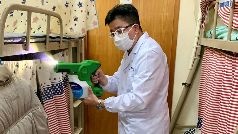A man demonstrates how to spray MAP-1, an antimicrobial coating that a team of university researchers claimed to be effective in killing virus, bacteria and spore, at a bedspace apartment in Hong Kong, China April 21, 2020. Picture taken April 21, 2020. REUTERS/Yoyo Chow