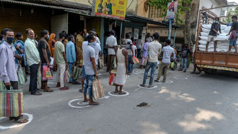 People stand in circles marked on the ground to maintain social distancing as they queue for food in Siliguri, India