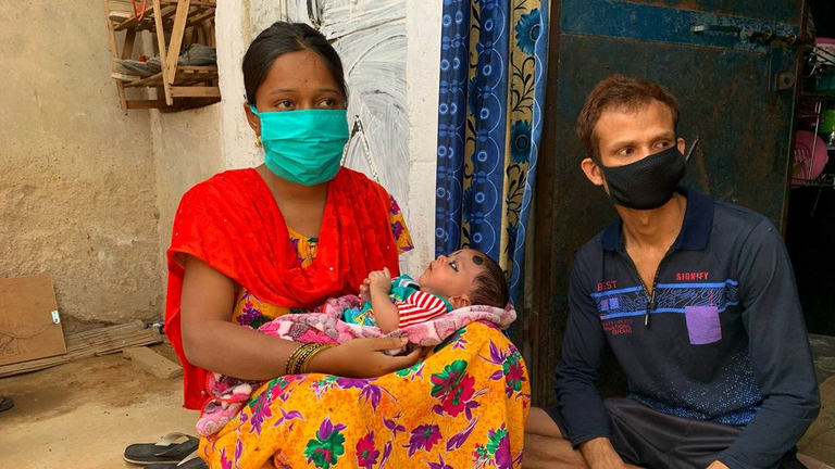 Mariam, left, and Mujibur with their child who was born during the lockdown