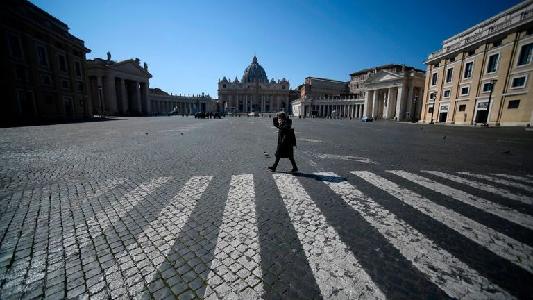 A woman walks across a deserted Pope Pius XII square in Rome