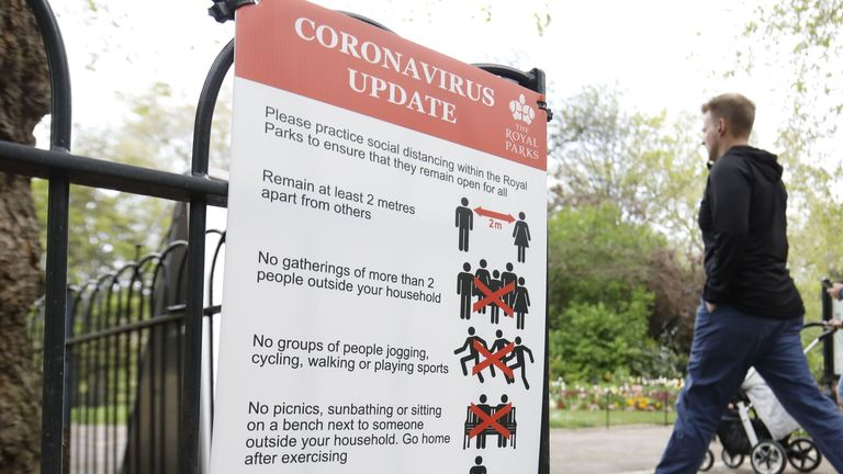 People walk past signs advising of social distancing rules in St James's Park in central London
