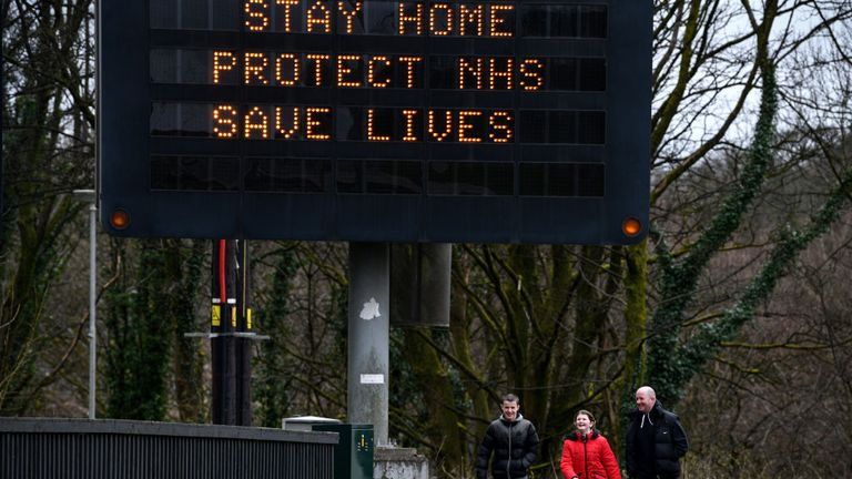 People walk under a sign warning Britons to stay at home during the coronavirus crisis