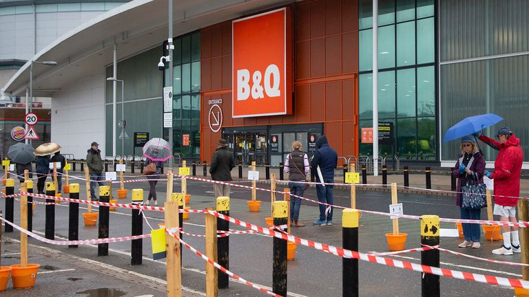 Members of the public shelter under umbrellas as they queue outside a branch of B&Q in Charlton, South London. Pic: George Cracknell Wright/LNP/Shutterstock