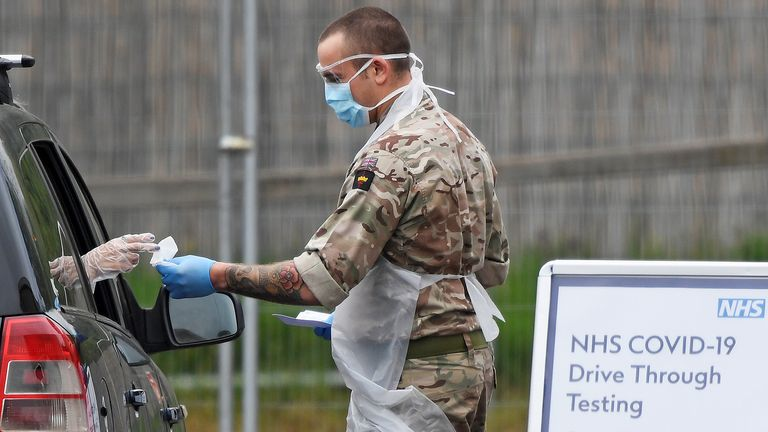 A member of the military tests a person at a coronavirus test centre in the car park of Chessington World of Adventures as the spread of the coronavirus disease (COVID-19) continues, Chessington, Britain, London, Britain, April 18, 2020. REUTERS/Toby Melville
