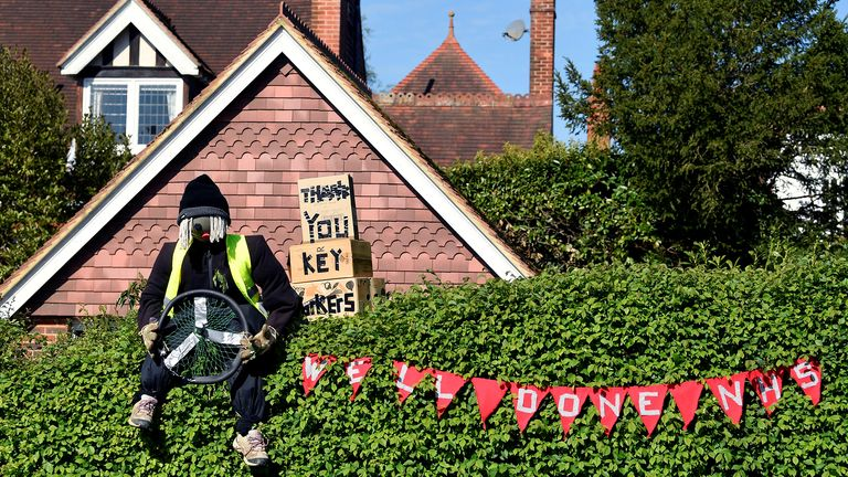 A figure representing a key worker is seen in a front garden, as various scarecrows lighten the daily lockdown walk, while the number of the coronavirus disease cases (COVID-19) grows around the world, in the village of Capel in southern Britain, April 26, 2020. Picture taken April 26, 2020. REUTERS/Toby Melville