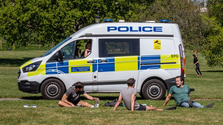 Three members of the public exercise as Police vans patrol Primrose Hill. Pic: Alex Lentati/LNP/Shutterstock