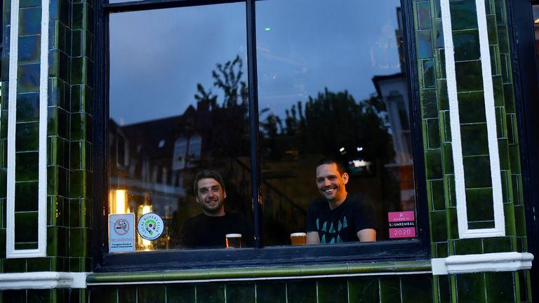 Dominic Townsend and Steve Pond enjoy a pint of beer as they look out from The Prince, a pub they share an apartment above and say are lucky enough to be stuck in during lockdown as the coronavirus disease (COVID-19) continues in London, Britain April 28, 2020. Picture taken April 28, 2020.  REUTERS/Dylan Martinez