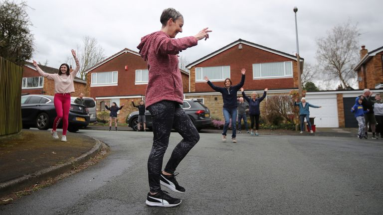 Janet Woodcock leads a dance class for residents in a street in Frodsham, as the spread of the coronavirus disease (COVID-19) continues, Frodsham, Britain, April 1, 2020. REUTERS/Molly Darlington