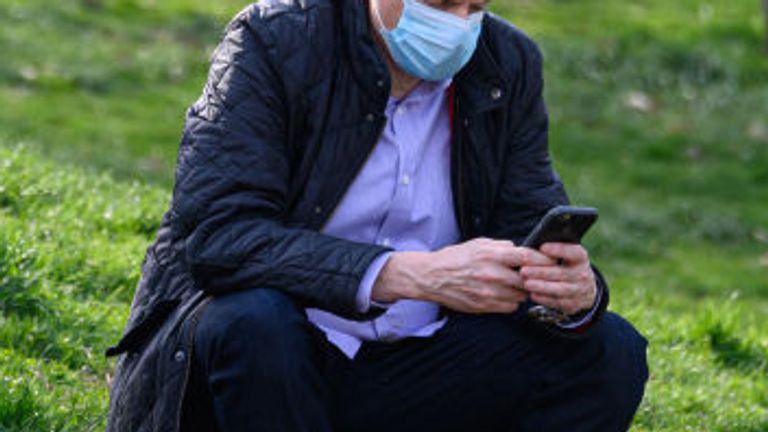 NEW YORK, NY - APRIL 12: A person wears a protective face mask while checking his phone in Central Park during the coronavirus pandemic on April 12, 2020 in New York City. COVID-19 has spread to most countries around the world, claiming over 110,000 lives with infections at over 1.8 million people. (Photo by Noam Galai/Getty Images)