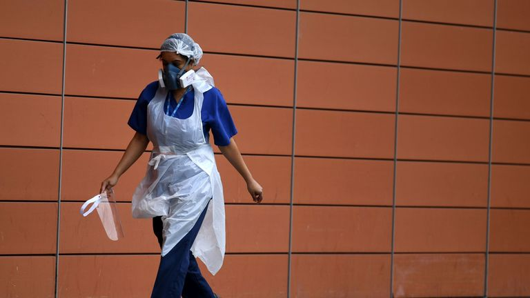 A nurse wears a protective face mask as she walks outside The Royal London Hospital in east London