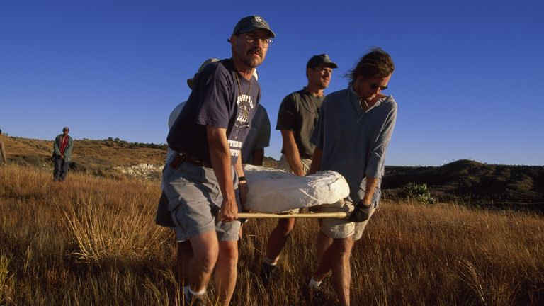 View of plaster jacket containing skeleton of Adalatherium huibeing carried from excavation site to road. Author David Krause at left front. Credit: National Geographic Society/Maria Stenzel.