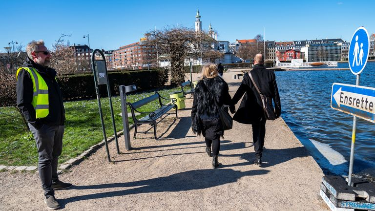 A park warden helps direct pedestrians to move one way only around a string of artificial lakes in Copenhagen
