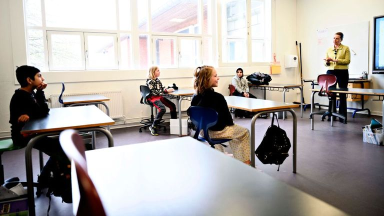 Danish Prime Minister Mette Frederiksen (R) speaks with pupils as she participates in the reopening of Lykkebo School in Valby in Copenhagen